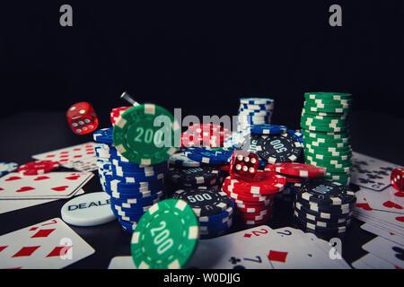 Close up pile de jetons de poker de différentes couleurs, jeux de cartes et dés plus isolés d'arrière-plan noir table de casino. Tournoi de Jeu gains, être