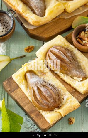 Dessert d'été. Des gâteaux feuilletés à la poire et farcie de crème de noix une table en bois rustique.