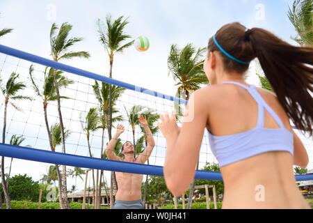 Les gens à jouer au volleyball de plage s'amusant dans le mode de vie actif sport. Frapper l'homme dans le jeu de volley-ball en été. La femme et l'homme modèle de remise en forme de vie sain vivant faire du sport sur la plage. Banque D'Images
