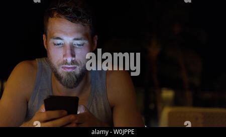 Man using smartphone à internet navigation de nuit mise à jour des médias sociaux. Jeune homme avec barbe à l'aide de mobile cell smart phone dans le noir en été. Banque D'Images
