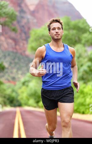 Sport et fitness runner homme qui court sur la formation pour faire de l'intervalle de marathon sprint entraînement en plein air en été. Modèle sport athlète masculin en bonne santé et souriant de leurs aspirations. Banque D'Images