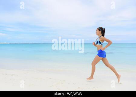 Mode de vie sain et actif d'exécution woman jogging sur la plage. Les jeunes adultes de sexe féminin pleine longueur faisant matin cardio pieds nus dans le sable blanc et océan turquoise background. Banque D'Images