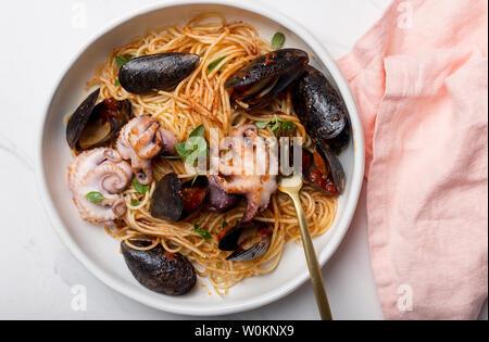 Pâtes aux fruits de mer et la sauce tomate. Spaghetti aux moules et poulpes dans bol blanc avec fourchette et serviette rose sur fond blanc. Concept d'seafoo Banque D'Images