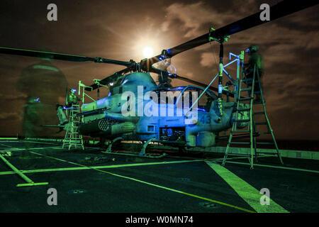 Les Marines américains avec l'escadron 161 à rotors basculants moyen Maritime, 15e Marine Expeditionary Unit, effectuer la maintenance après-vol sur un AH-1Z Viper à bord du USS Anchorage dans la mer des Philippines, le 2 juin 2015. U.S. Marine Corps photo par le Sgt. Jamean Berry/UPI