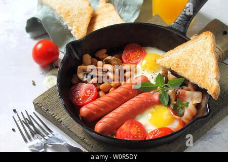 Petit-déjeuner en anglais oeufs brouillés avec bacon, haricots, champignons, saucisses et les tomates de la lumière table en pierre. Espace libre pour votre texte. Banque D'Images