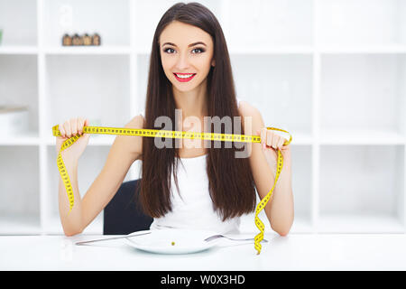 Régime alimentaire. Happy young smiling woman sur le point de manger une plaque de maintien de pois et la fourche avec ruban à mesurer. Banque D'Images