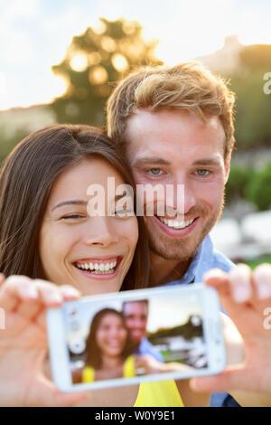 Couple in love de prendre photo avec selfies smartphone. Mixed Race couple romantique en tenant vos autoportraits photos avec smart téléphone appareil s'amuser ensemble en plein air dans le parc. Fille asiatique, Guy de race blanche. Banque D'Images