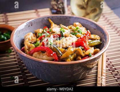 Faire revenir le poulet, les courgettes, poivrons et l'oignon vert. La cuisine asiatique Banque D'Images