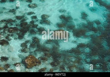 Close up de roches au fond de la mer à l'eau bleu clair avec du sable entre les deux. Banque D'Images