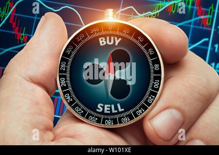 Hand holding compass avec symbole d'ondulation rougeoyant et devant les données de la bourse. Aiguille de la boussole montrant buy word. Banque D'Images