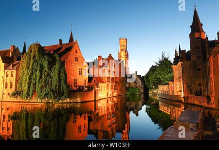 Vue sur la célèbre attraction touristique de Bruges - Rozenhoedkaai vue canal avec beffroi et maisons anciennes le long de canal avec arbre dans la nuit. Bruges, Belgique