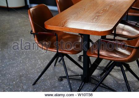 Table en bois et de fauteuils en cuir ou des chaises, dans un café, bureau ou chambre. Design élégant, style vintage. L'espace pour le petit-déjeuner, les réunions d'affaires et corpor Banque D'Images