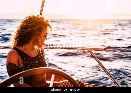 Belle belle blonde curly femme adulte à l'océan, bénéficiant d'un voyage et billet sur sail yacht - nouvelle génération de personnes jouissent de la liberté et un