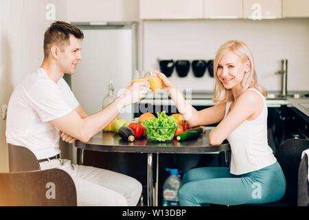Belle Jeune couple dans l'amour de manger de délicieux petit déjeuner tôt le matin ensoleillé dans la cuisine et passer un bon moment. L'alimentation saine, vegetar Banque D'Images