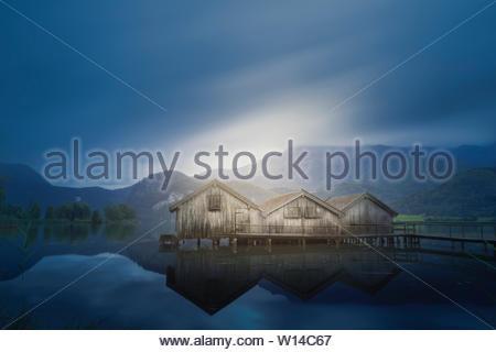 **Cabines pour stocker du matériel de pêche**quelques cabines sur un lac dans le sud de l'Allemagne lors d'un ciel nuageux matin d'été photographié avec une longue exposition Banque D'Images