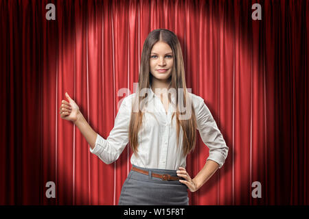 Avant petit view of young attractive businesswoman avec de longs cheveux droits debout dans spotlight contre rideau de scène rouge et faire thumbs-up. Banque D'Images
