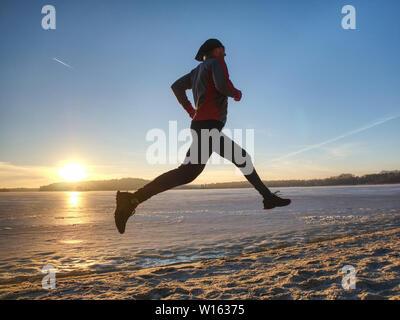 Les coureurs couple en hiver la nature. Frozen river beach. Copier l'espace. Banque D'Images