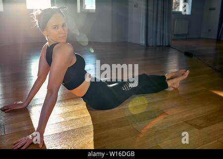 Matin girl doing yoga des exercices d'étirement dans la chambre pour le Pilates. Belle Lumière, de photos aériennes, d'un mode de vie sain, les hormones du corps et âme