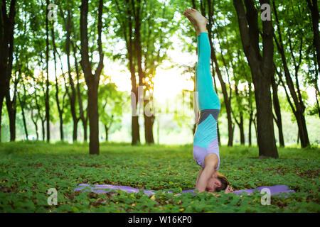 Fille brune mince debout dans la tête de l'exercice, salamba sirsasana poser dans un parc d'été sur un fond coucher de soleil. Femme de faire les exercices sur le yoga m Banque D'Images