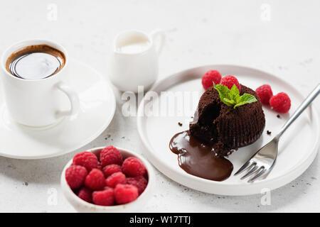 Délicieux Fondant au chocolat ou gâteau de lave sur plaque blanche servi avec une tasse de café noir, de crème et de framboises Banque D'Images