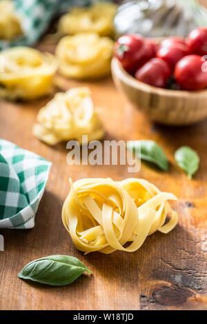 Les pâtes italiennes tagliatelles sur table avec le basilic et les tomates