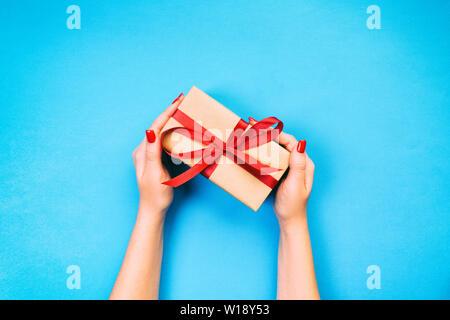 Femme mains donner enveloppé valentine ou autres faits main de vacances présents dans le papier avec un ruban rouge. Présent fort, décoration de table, cadeaux sur bleu Vue de dessus Banque D'Images
