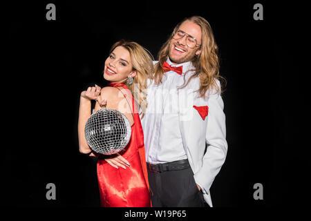Cheerful blonde girl holding boule disco brillant et souriant près de l'Homme à lunettes isolated on black Banque D'Images