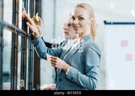 Selective focus of cheerful blond businesswoman putting sticky note sur l'homme près de la fenêtre Banque D'Images