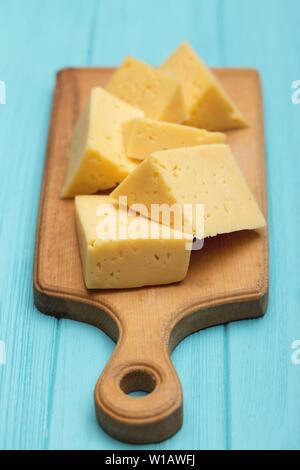 Fromage sur une planche à découper sur un fond bleu Banque D'Images