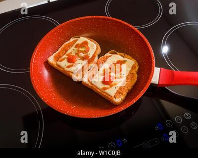 Le pain dans la poêle rouge sur la table de cuisson à induction