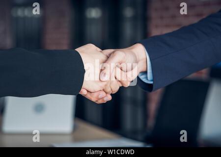 Close up handshake entre young à salle de réunion dans un bureau moderne