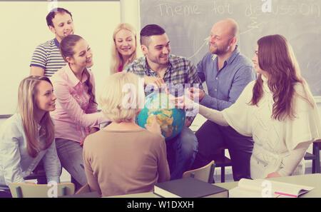 Les élèves du secondaire d'avoir du plaisir avec une Classe de géographie au monde lors d'une pause dans une salle de classe Banque D'Images