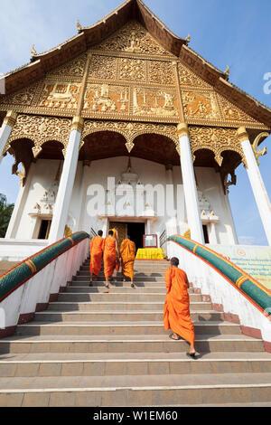 Les moines bouddhistes, monter les escaliers à un temple au Pha That Luang, Vientiane, Laos, Indochine, Asie du Sud-Est, l'Asie Banque D'Images