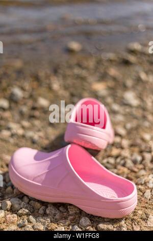 Paire de sabots en plastique rose sur la plage en été Banque D'Images