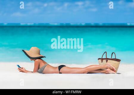 Beach Vacation girl using mobile phone app sms sms ou le partage de photos sur les médias sociaux au cours de voyages d'été. Bikini woman relaxing bronzer sur le sable se trouvant sur le port de serviettes sun hat. Banque D'Images