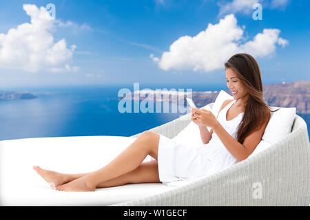 Asian woman using phone app détente sur lit de repos sur une terrasse extérieure. Accueil vivant à l'extérieur meubles de patio. Les jeunes adultes texting on smartphone lying on sofa avec arrière-plan Oia Santorini profitant de l'été.