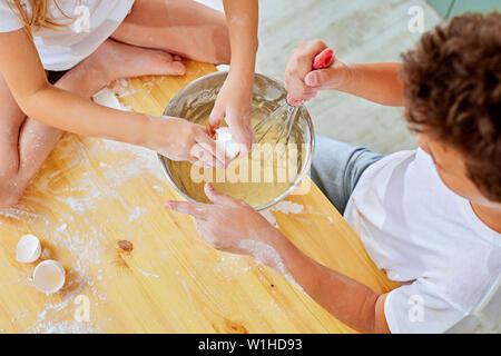 Les petites mains de l'enfant battre la pâte pendant la cuisson des pancakes dans la cuisine Banque D'Images