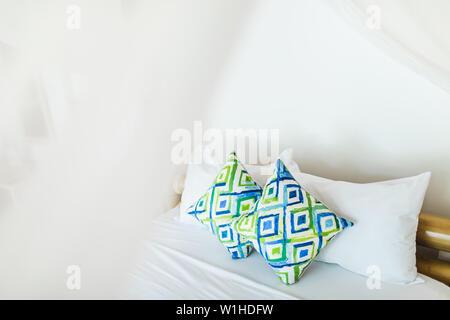 Bleu et vert coloré deux oreillers décoratifs sur lit blanc. Design intérieur confortable léger. Lieu vide. Banque D'Images