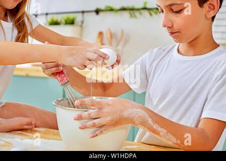 Frère et soeur de la mère à l'aider à préparer dans la cuisine Banque D'Images