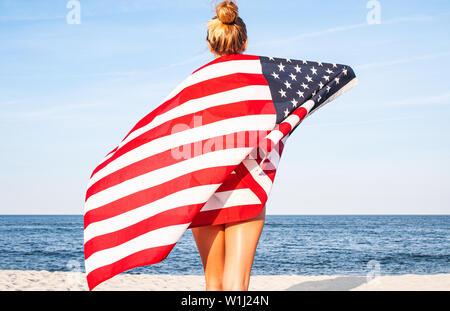 Belle femme patriotique avec le drapeau américain sur la plage. USA Le jour de l'indépendance, 4 juillet. Concept de la liberté, vue de l'arrière.