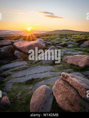 Scène Coucher du soleil dans les régions rurales de Peak District, Derbyshire, UK.des pierres en haut de la colline éclairée par horizon soleil derrière.Ethereal soir paysage.ima Paysage