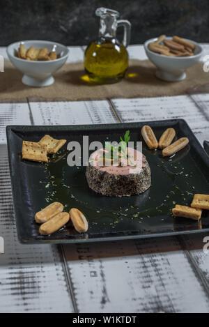 Pate de canard au poivre servi sur une plaque noire avec des croûtons de pain Banque D'Images