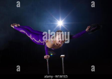 L'actrice de cirque effectue le nombre dans une belle fumée. Équilibre manuel sur les cannes. Fille souple corps.Performance d'un gymnaste de l'air dans un cirque Banque D'Images