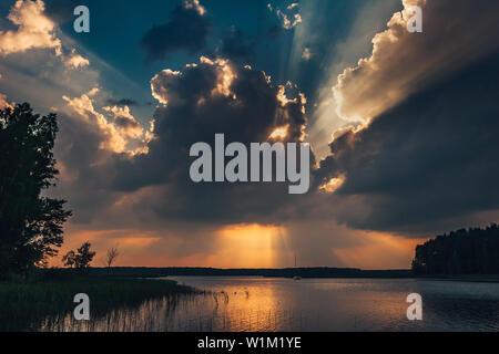 Ciel coucher épique sur le lac. De beaux rayons de soleil passant à travers les nuages orageux dramatiques. Un paysage extraordinaire. Banque D'Images