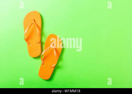 Tongs orange sur fond vert. Vue de dessus avec l'exemplaire de l'espace. Banque D'Images