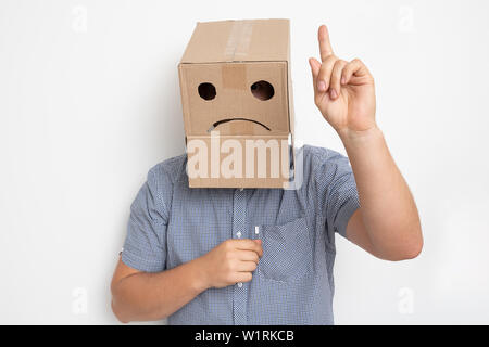 Description: un homme avec une boîte en carton sur la tête, un smiley triste Banque D'Images