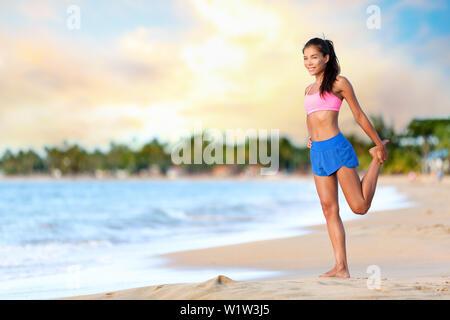 Happy young woman doing stretching exercice sur la plage. Female est wearing sports bra and shorts. Toute la longueur de sporty woman tout en s'exerçant sur la mer contre ciel nuageux. Banque D'Images