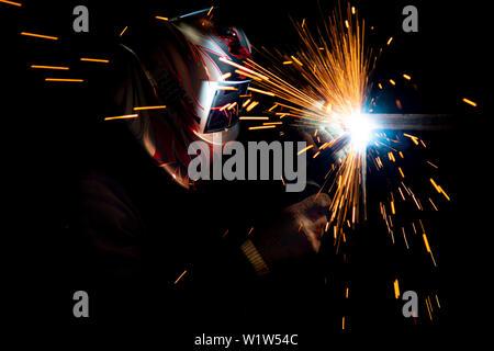 Soudeur mâle dans un masque d'effectuer la soudure de métaux. photo en couleurs sombres. Des étincelles voler. Banque D'Images