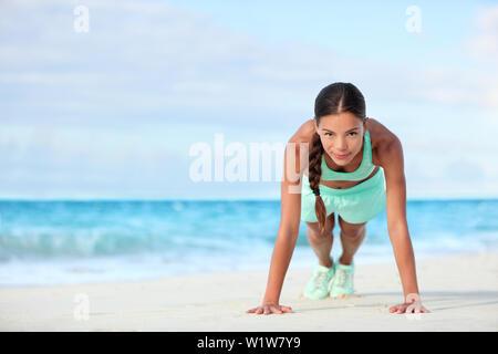 Plage Fitness woman smiling planking faisant les exercices de yoga. Happy Asian girl sa formation l'exercice de ses muscles de base abs avec la planche. Banque D'Images