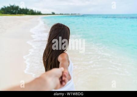 Vacances d'été Couple - Voyage femme marche sur lune de miel romantique beach holidays holding hand d'après son petit ami, vue de derrière. POV. Banque D'Images